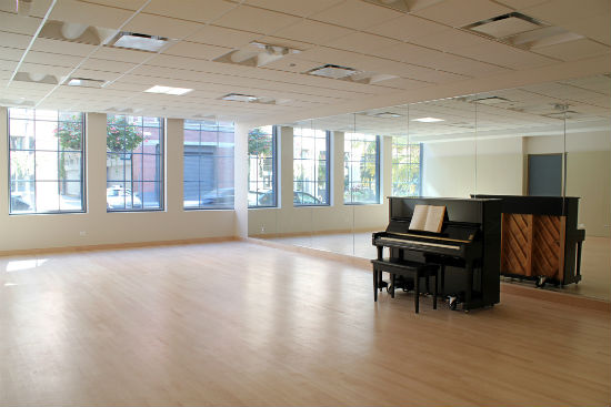 A large room with many light-filled windows, a wall-length mirror, an upright piano and wood floor