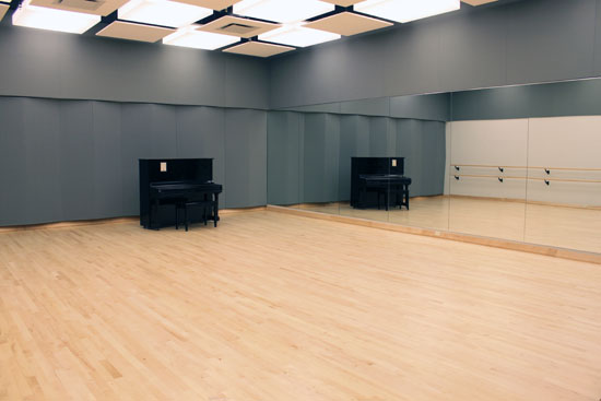 Large Audition Room with soundproofing on the far wall, an upright piano in the corner, a mirror on the near wall and barres visible in the reflection of the opposite wall.
